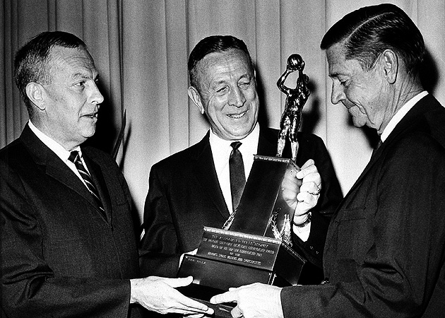 John Wooden (center) receives the AP championship trophy for his 1964 national championship season, in which his Bruins won 30 straight games.