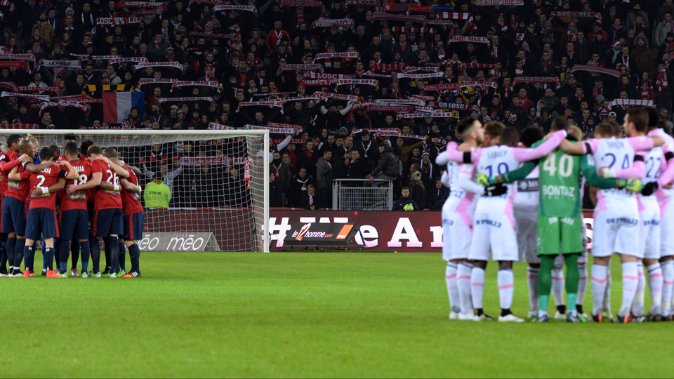 Players from Lille and Evian observe a moment of silence following Wednesday's tragic attack in Paris.