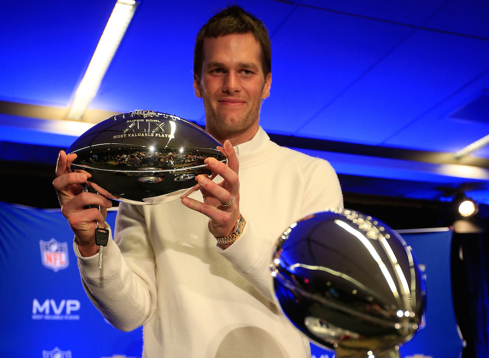 Tom Brady holds the Super Bowl XLIX MVP trophy.