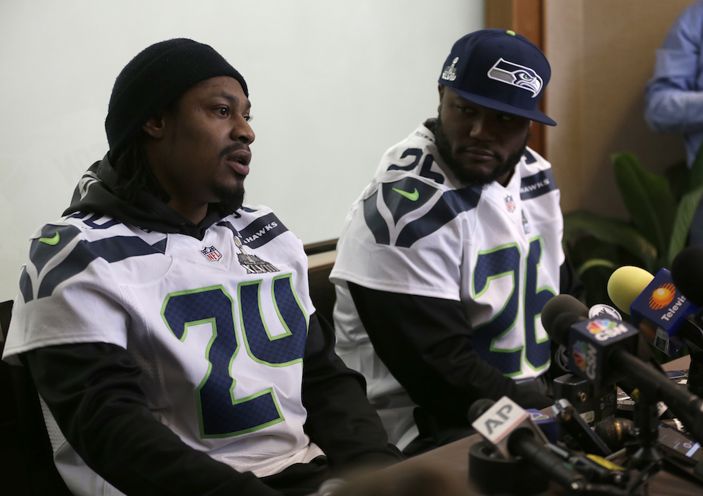 Seattle Seahawks running back Marshawn Lynch (left) and former teammate Michael Robinson take part in a Super Bowl XLVIII media availability on Jan. 30, 2014.