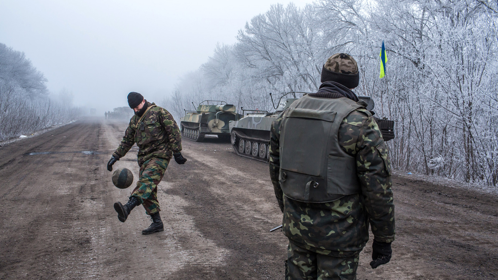 Ukrainian soldiers play football on the road leading to the embattled town of Debaltseve on February 15, 2015 outside Artemivsk, Ukraine