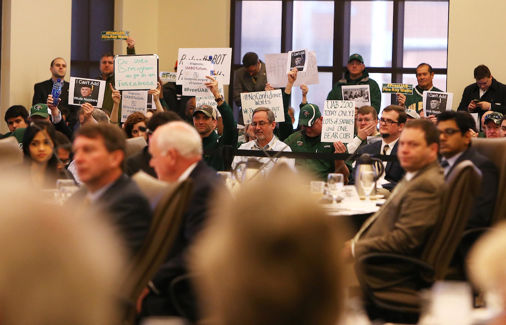 Protesters hold signs in opposition to UAB president Ray Watts on Feb. 6.
