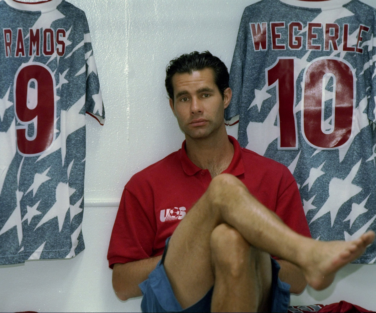 With Tab Ramos's and his own denim USA jersey draped above him, Roy Wegerle sits in the locker room prior to taking on Switzerland in the 1994 World Cup.