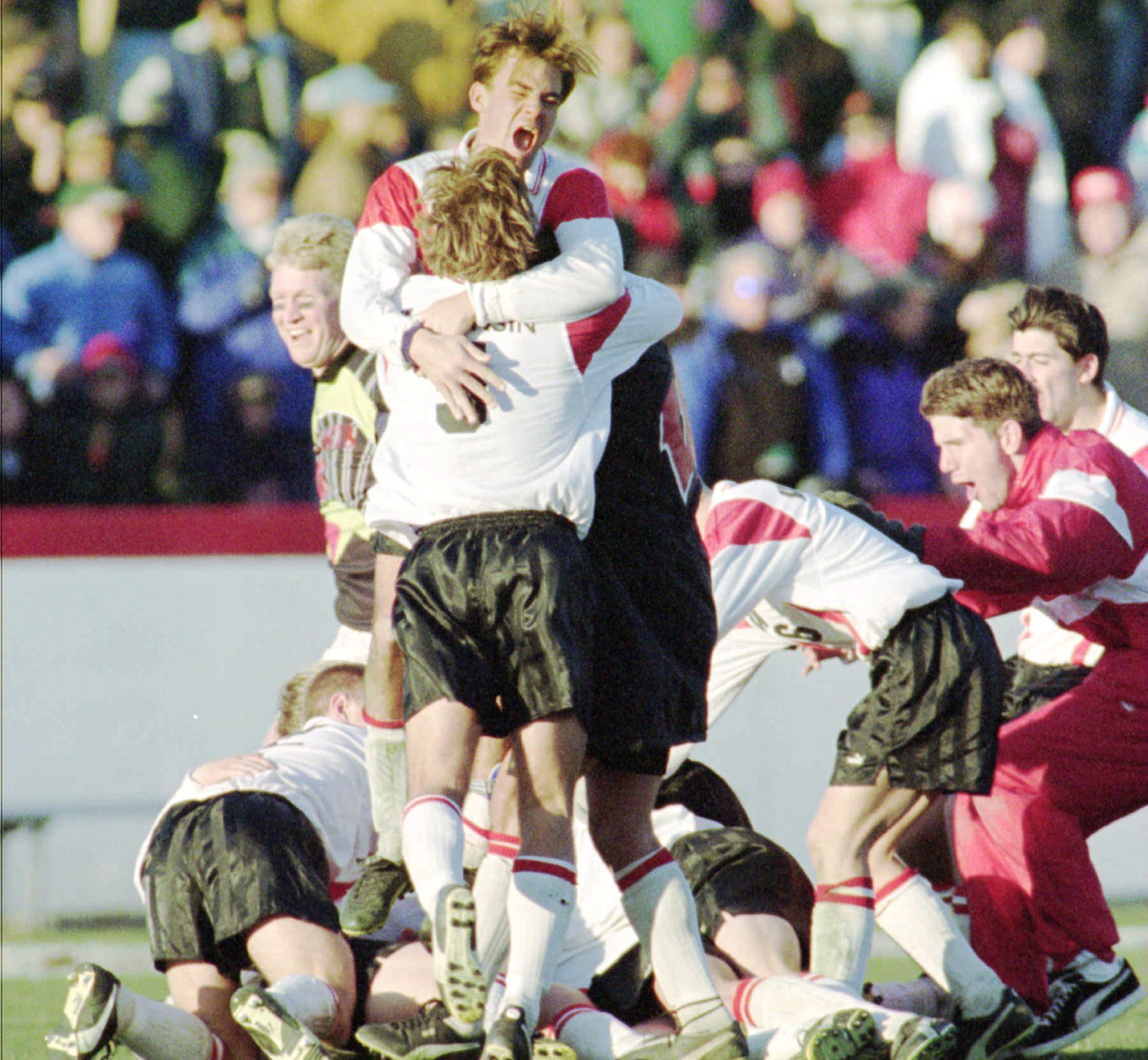 Wisconsin players mob one another after winning the school's first NCAA men's soccer championship.