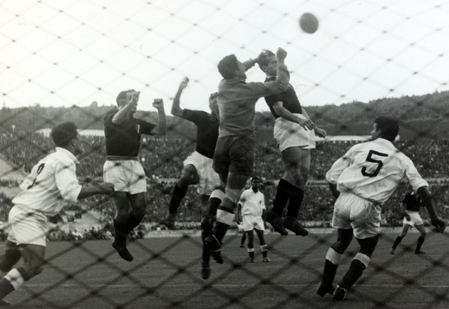 Benfica goalkeeper Pinto Machado punches the ball away under pressure from Torino's Romeo Menti, Émile Bongiorni and Valentino Mazzola a day before a tragic plane crash killed the Italian team.