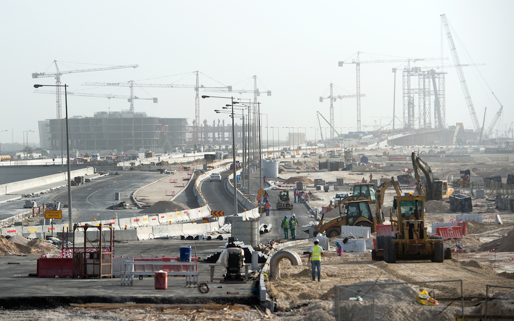 Builders and construction vehicles at work on a construction site in Doha, Qatar, on March 10, 2015.