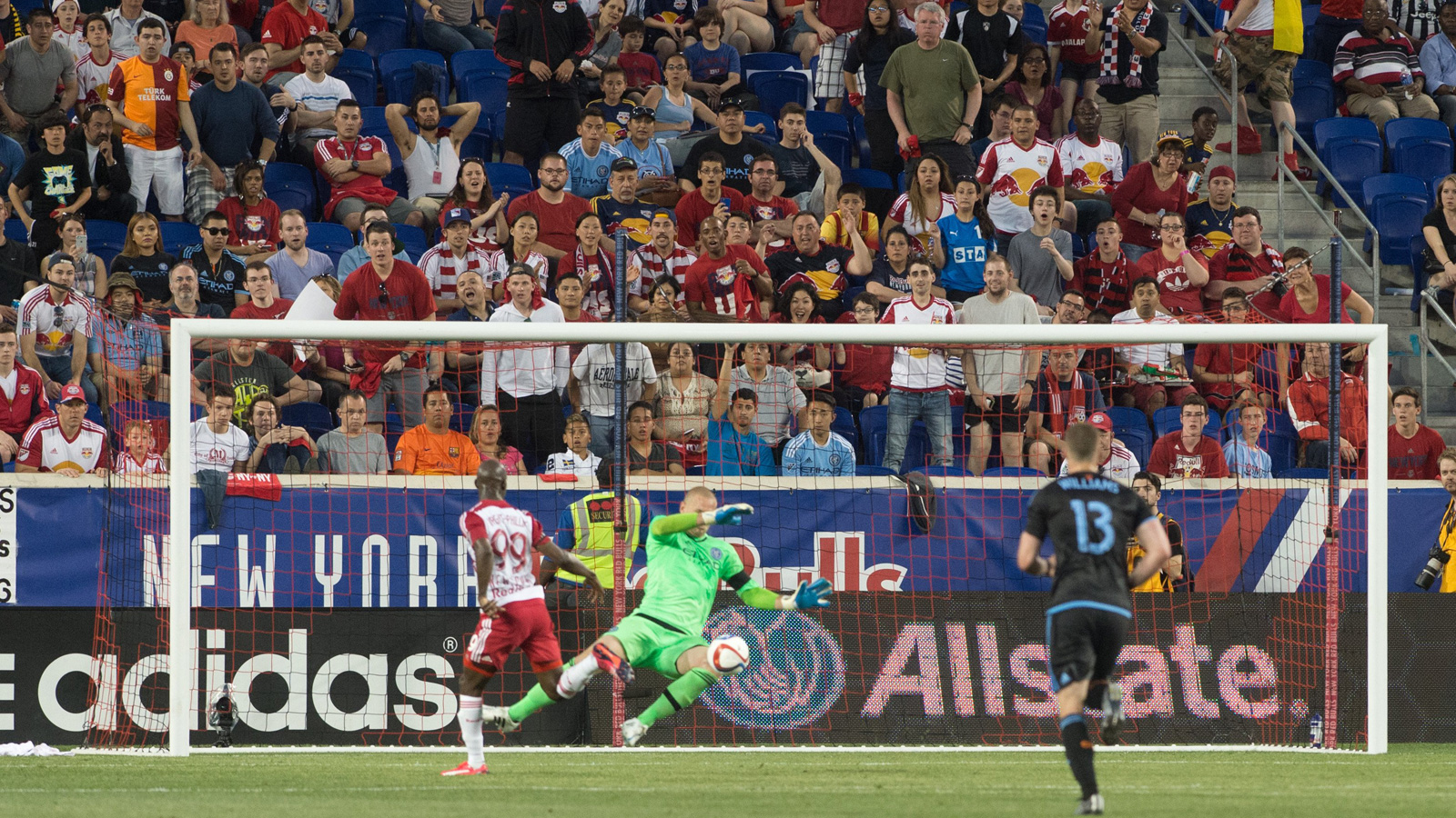 NYCFC goalkeeper Josh Saunders makes a save on Red Bulls forward Bradley Wright-Phillips in the inaugural match between the two clubs, won by the Red Bulls 2-1.