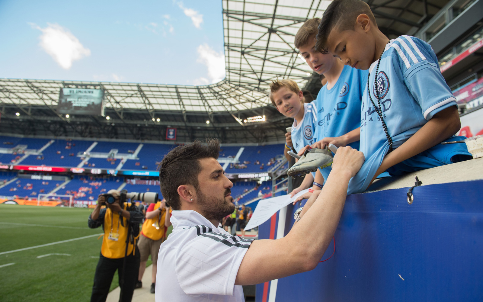 David Villa signs an autograph for a young NYCFC fan at Red Bull Arena in the club's first match against the New York Red Bulls.