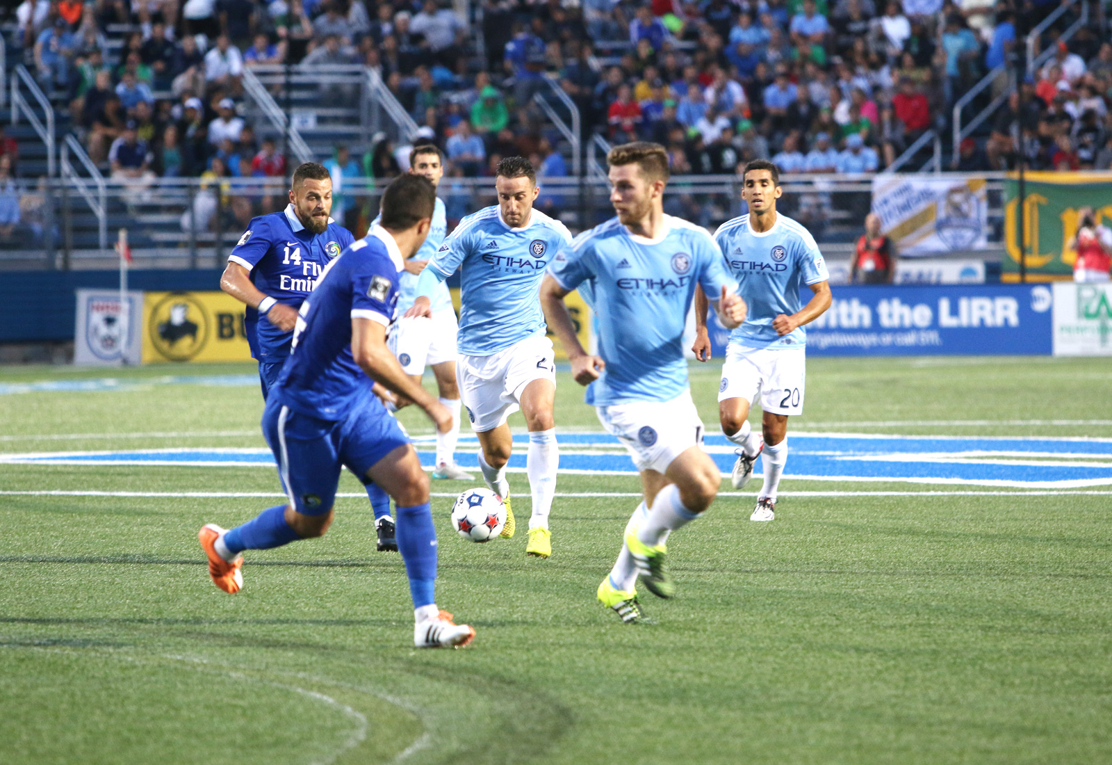NYCFC defender R.J. Allen pushes the ball across midfield surrounded by a trio of teammates and two Cosmos defenders during the first half of their U.S. Open Cup fourth-round match