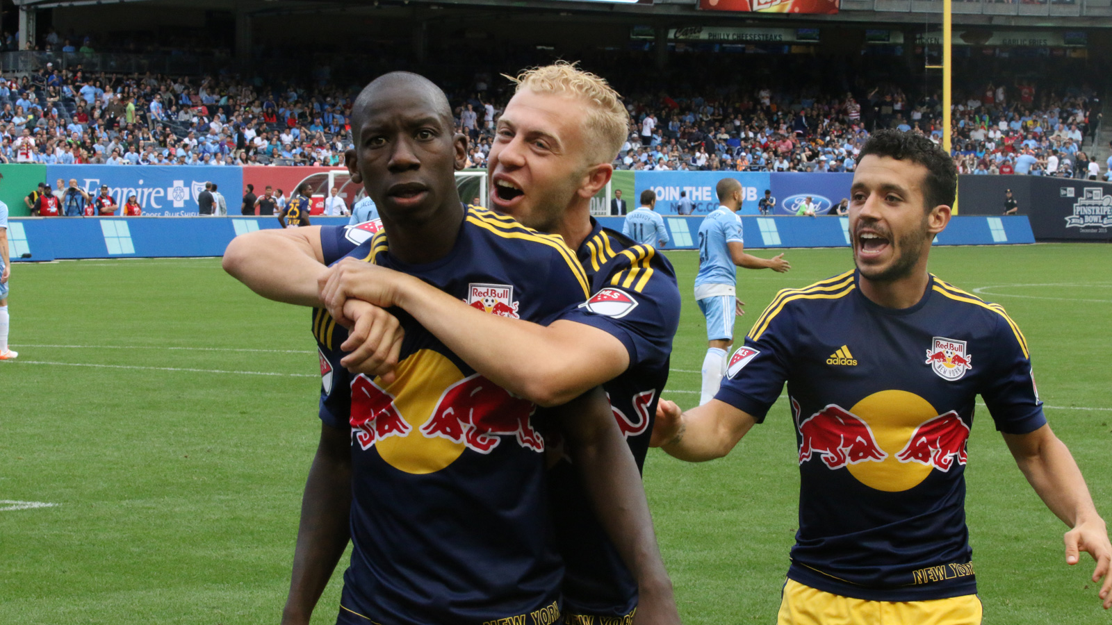 New York Red Bulls striker Bradley Wright-Phillips (left) celebrates with fellow striker Mike Grella (middle) and midfielder Felipe (right) after scoring the Red Bulls' first goal of the match, which tied the game less than two minutes into the second half.