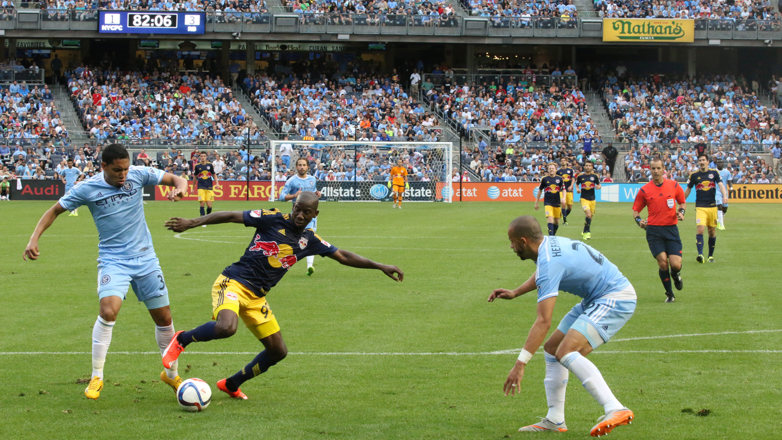 New York Red Bulls striker Bradley Wright-Phillips (99) gets technical with the ball, controlling it while under pressure from NYCFC defender Jason Hernandez (21) and midfielder Javier Calle (30).