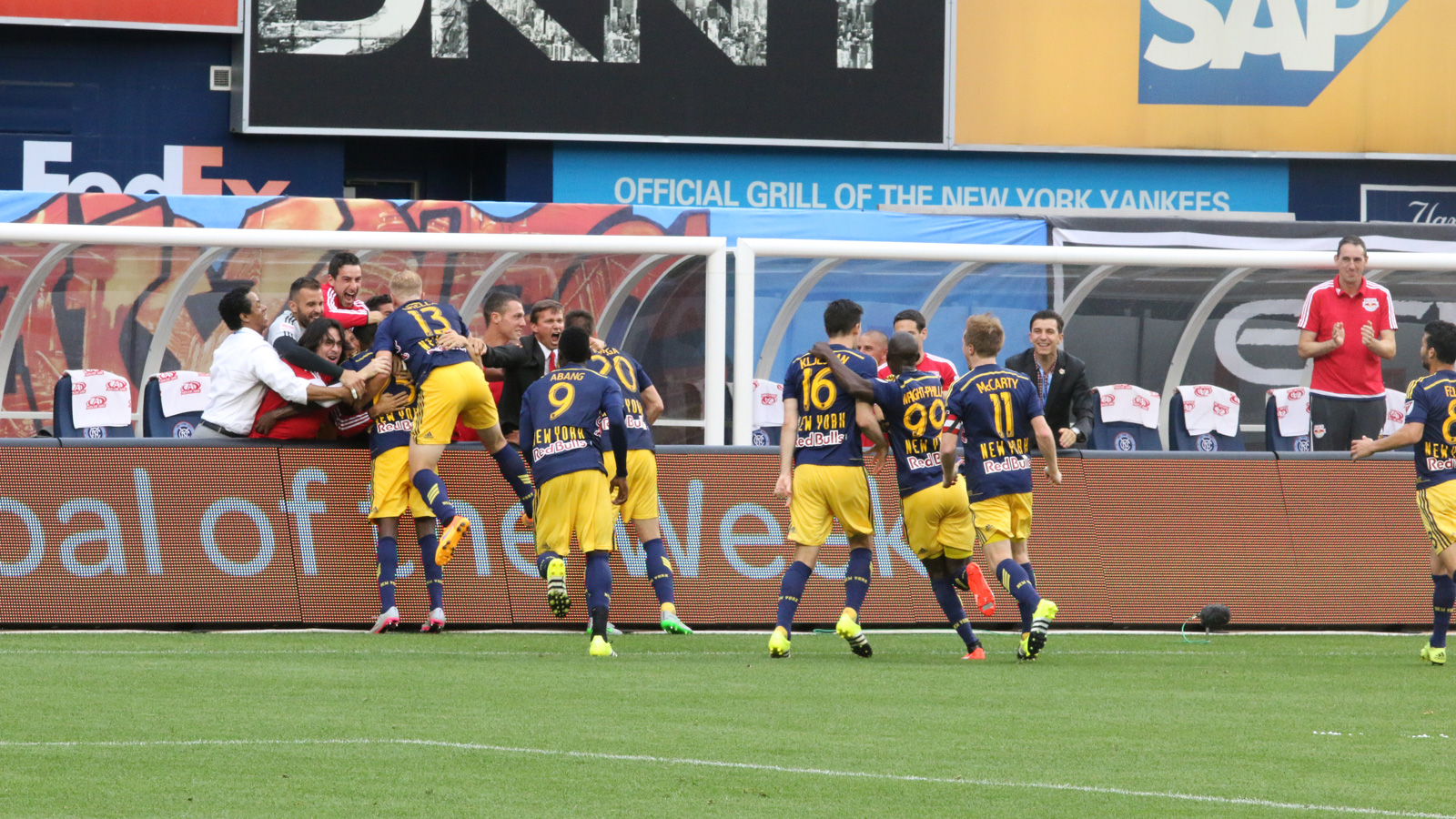 The New York Red Bulls run over to their bench to celebrate defender Chris Duvall's (25) first goal in Major League Soccer. Strikers Mike Grella (13) and Anatole Abang (9) and defender Matt Miazga (20) join coach Jesse Marsch in the post goal embrace.
