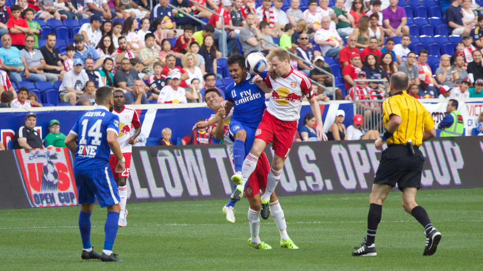 New York Red Bulls captain Dax McCarty (right) and Cosmos midfielder Andrés Alexander Flores Mejía (center) meet each other at the ball mid-flight in the first half of their U.S. Open Cup fifth-round match.