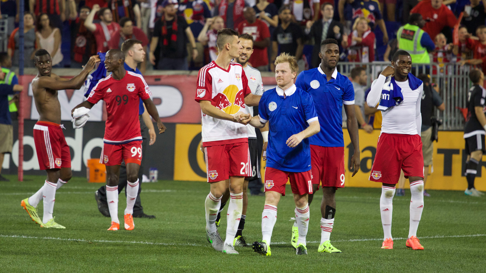 Red Bulls striker Anatole Abang (far right), captain Dax McCarty (middle), defender Anthony Wallace (left) and midfielder Dane Richards (far left) make their celebratory lap around Red Bull Arena with the blue jerseys they exchanged with members of the New York Cosmos. Defender Matt Miazga (20) and striker Bradley Wright-Phillips (99) are also pictured.