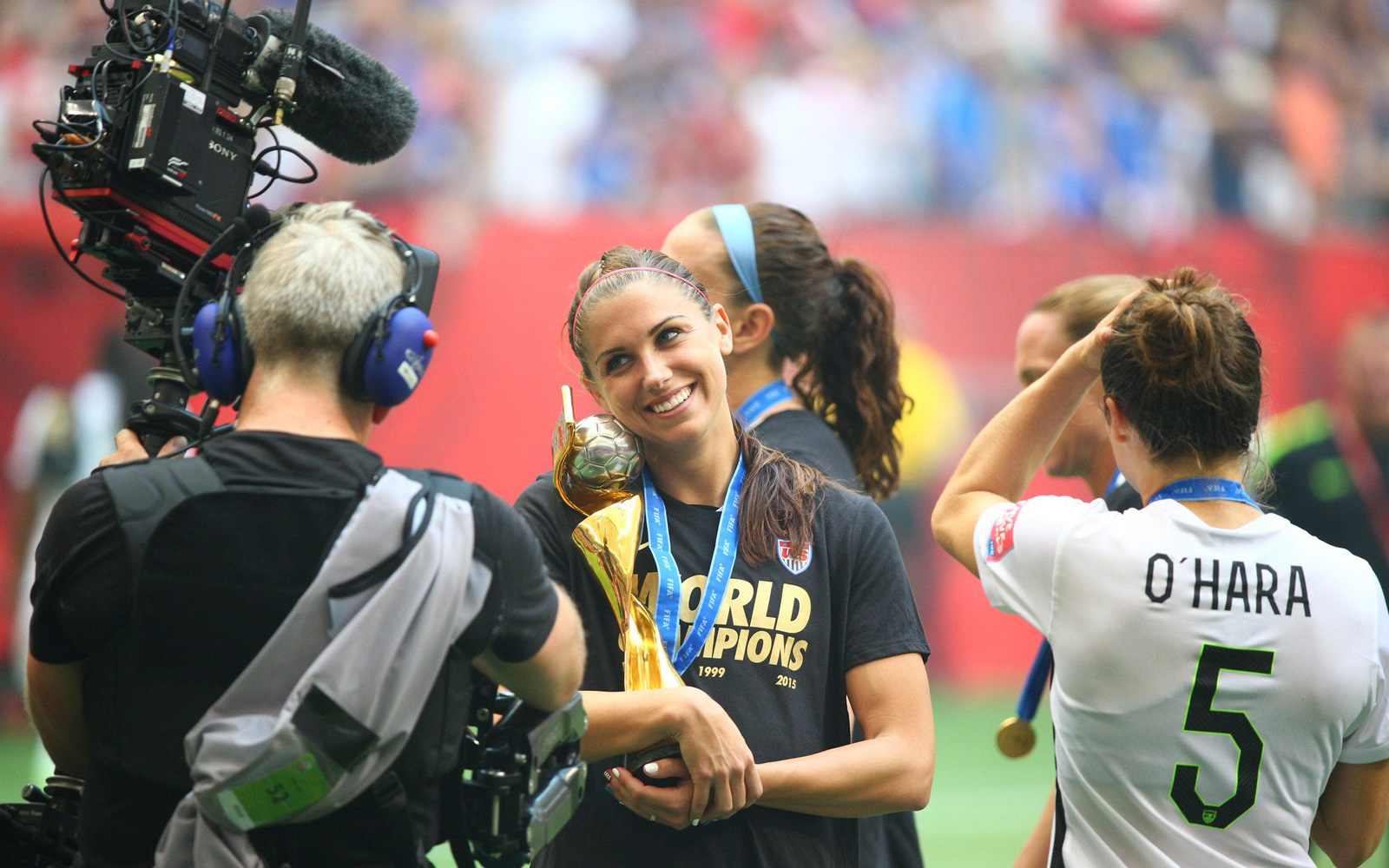 Alex Morgan smiles with the Women's World Cup trophy after the USA beat Japan 5-2 in the final