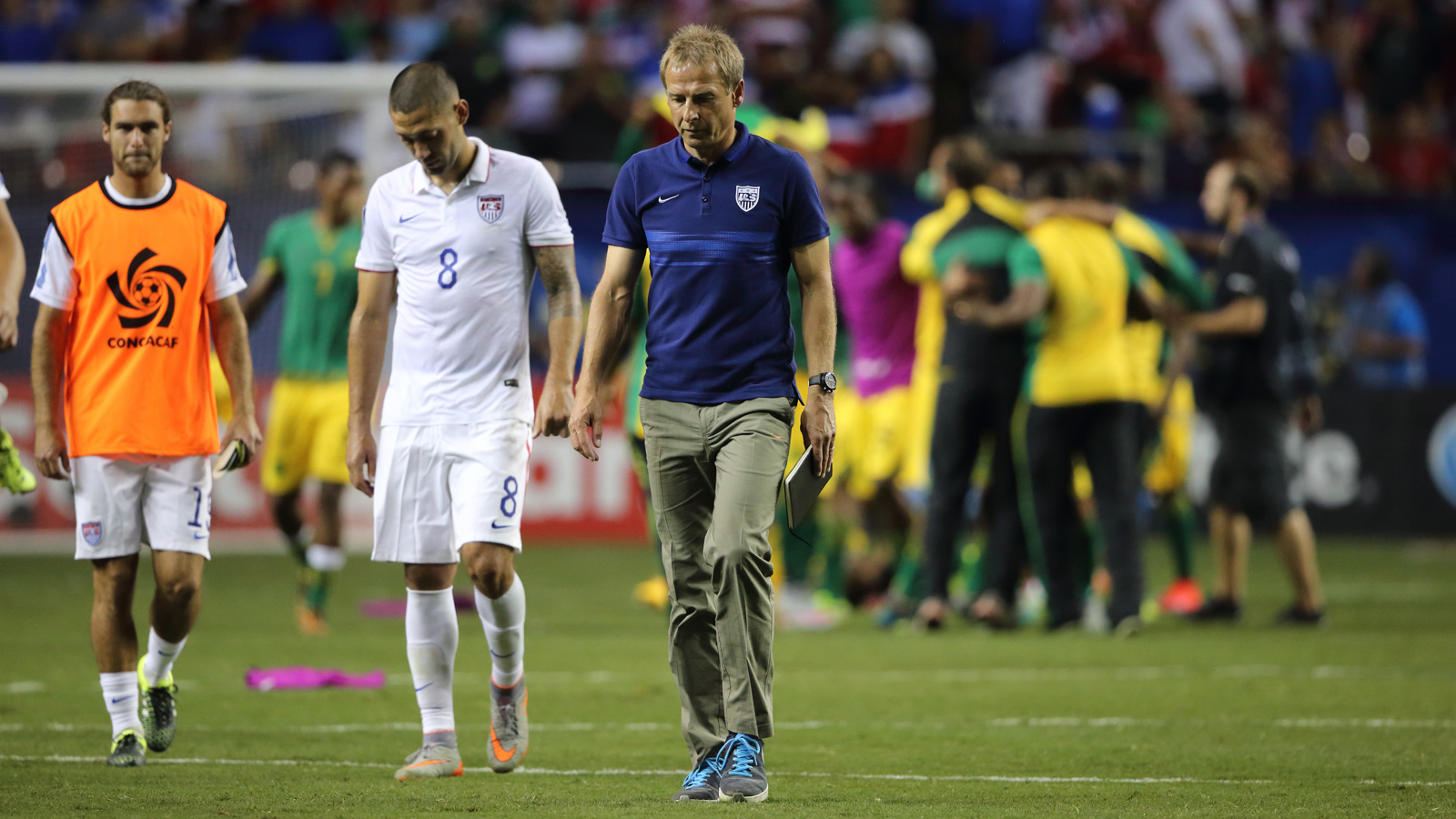 A downtrodden Clint Dempsey and Jurgen Klinsmann walk off the field as Jamaica celebrates a stunning 2-1 win over the USA in the CONCACAF Gold Cup semifinals.