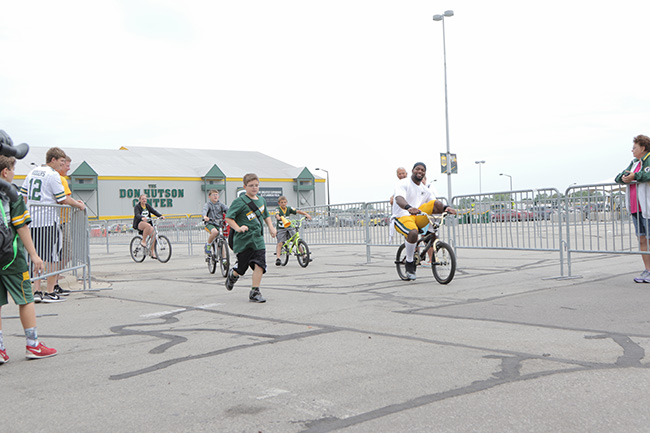 GREEN BAY, WIS. — It's a summer Packers tradition for a young fan to run alongside as a player rides the boy's bike from Nitschke Field to the parking lot after practice.