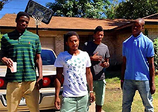 Johnathan Turner (left), Willie Hollins (second from left) and Troy Causey (right) stand in front of Willie's house with another young man.