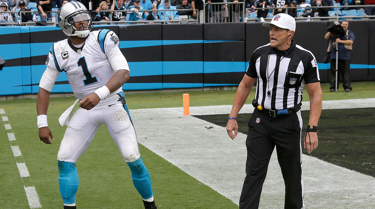 Cam Newton and Ed Hochuli have differing accounts of how this conversation went during Sunday's game. (Bob Leverone/AP)