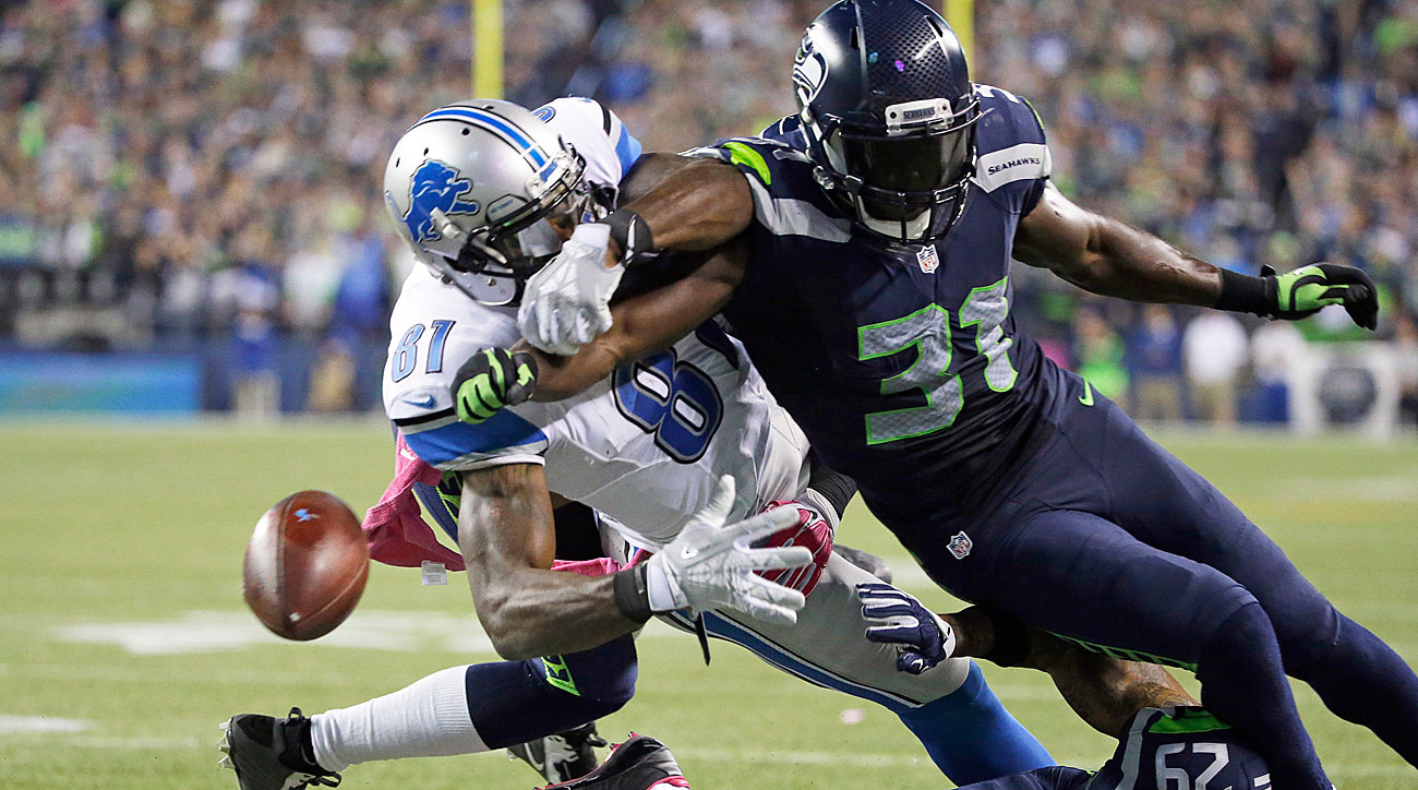 Kam Chancellor of the Seahawks knocks the ball away from the Lions' Calvin Johnson at the goal line.