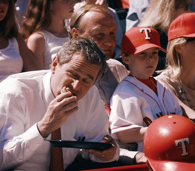 Former president George W. Bush eats a hot dog in the stands as part owner of the Texas Rangers in 1998.
