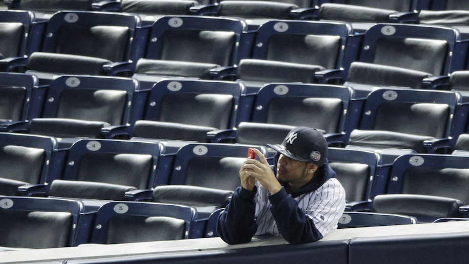 A lone New York Yankees fan sits in the midst of Yankee Stadium.