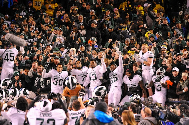 The Michigan State football team celebrates in the stands of Michigan Stadium after defeating the Wolverines 27-23 on October 17, 2015.