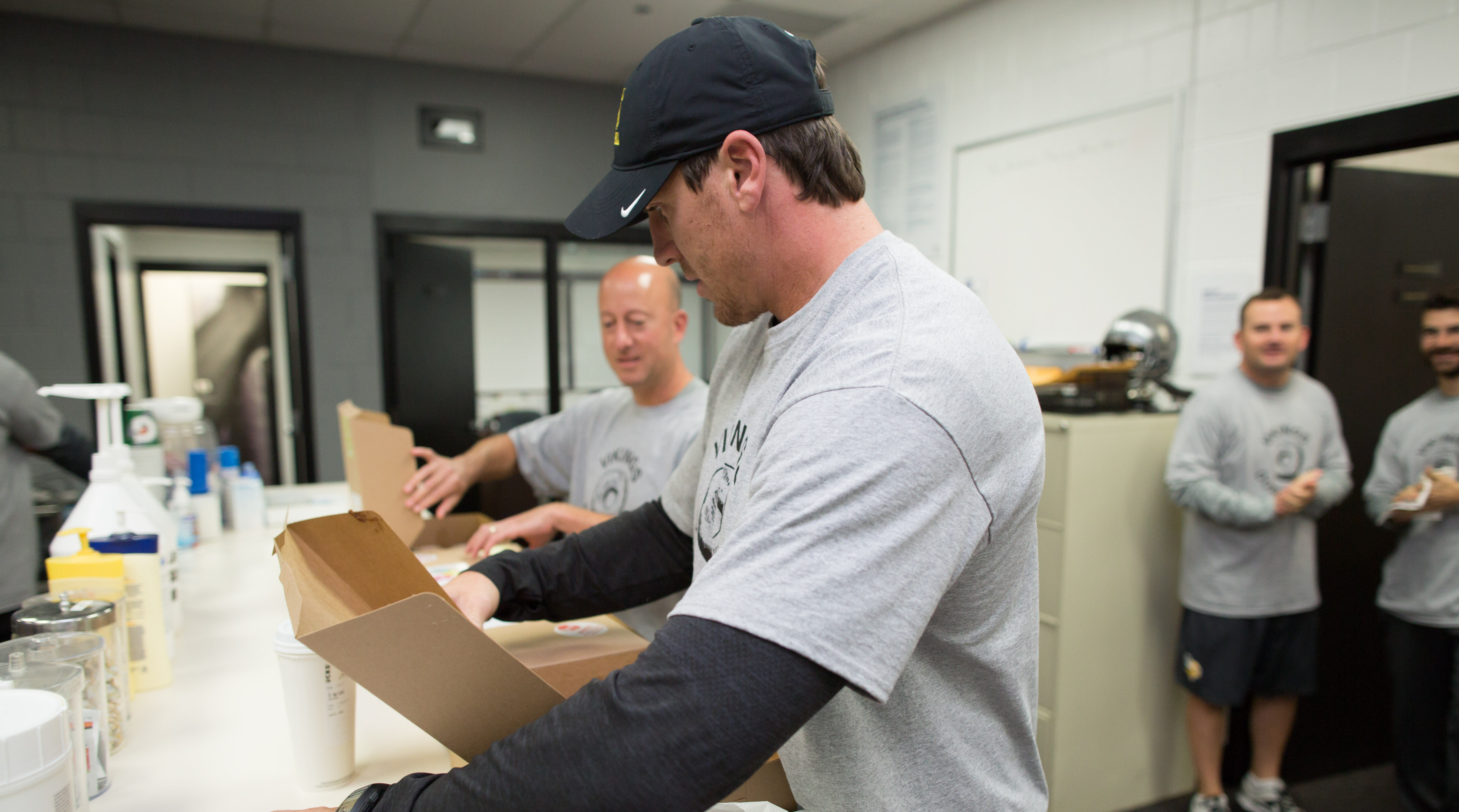 Donut Club president Eric Sugarman and board member Chad Greenway open the boxes to begin the viewing period.