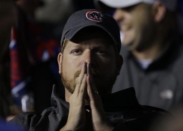 A Chicago Cubs fan prays.