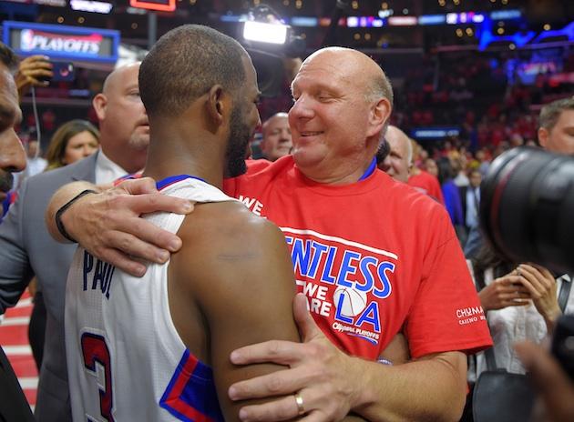 Los Angeles Clippers point guard Chris Paul (l) embraces owner Steve Ballmer (r).