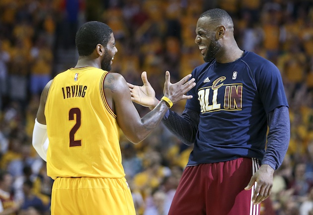 Kyrie Irving (l) and LeBron James (r) trade dap during a Cleveland Cavaliers game.