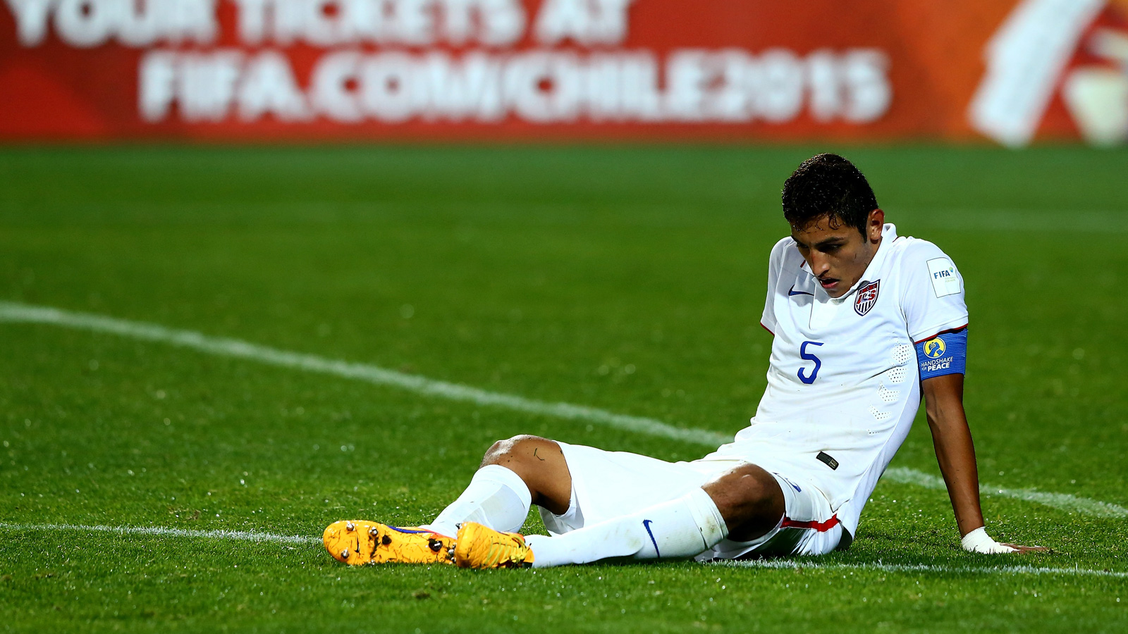 USA U-17 captain Hugo Arellano sits dejected after a 4-1 loss to host Chile eliminated the Americans from the World Cup in the group stage.