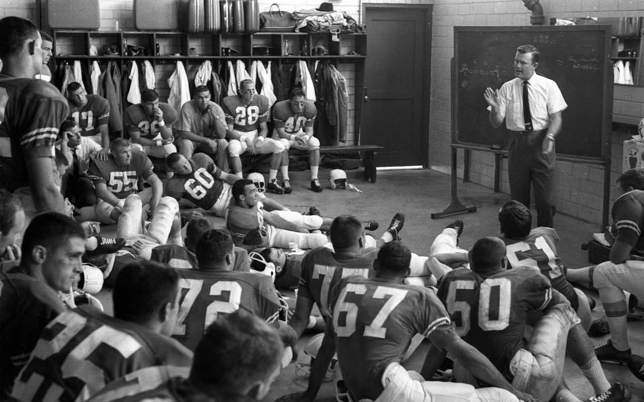Texas coach Darrell Royal talking to Tommy Nobis (60) and rest of the team in locker room before game vs Oklahoma at Cotton Bowl Stadium.