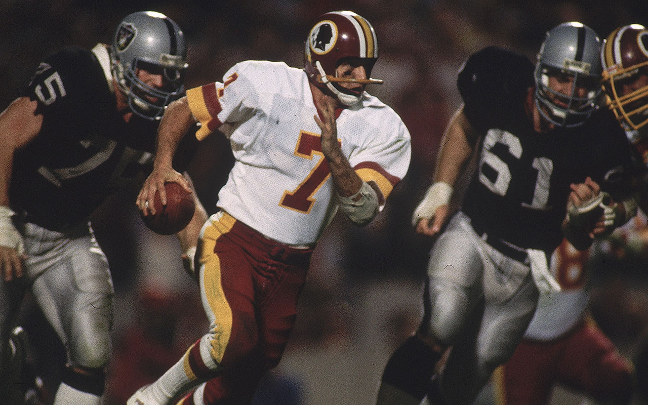 Super Bowl XVIII: Washington Redskins QB Joe Theismann #7 in action scrambling during game vs Los Angeles Raiders.