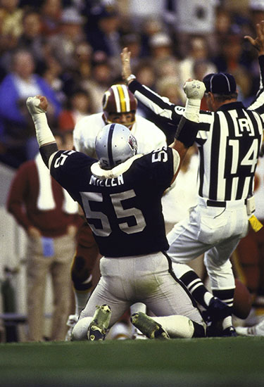 Super Bowl XVIII. Rear view of LA Raiders Matt Millen #55 on field kneeling after sacking Wash. Redskins QB Joe Theismann