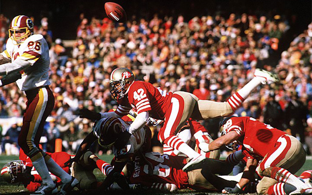 49ers Ronnie Lott pops the ball loose during a 1984 NFC playoff game against the Wash. Redskins.