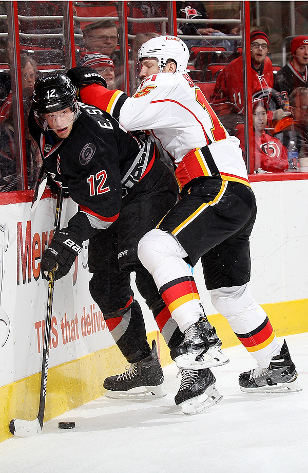 Ladislav Smid of the Calgary Flames checks Eric Staal of the Carolina Hurricanes at PNC Arena in Raleigh, N.C.