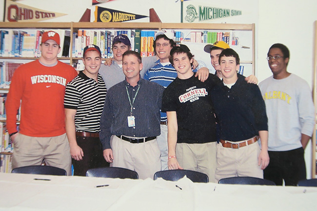 Specht (middle, blue dress shirt) and his players on signing day. Kuechly is in the middle of the back row, wearing a white Boston College hat.