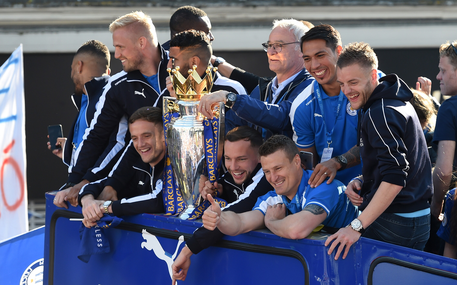 Flanked by his star players, Leicester manager Claudio Ranieri shows off the Premier League trophy.