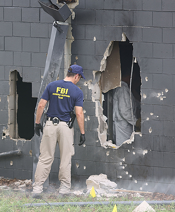 An FBI agent investigates the back wall of Pulse Nightclub in Orlando.