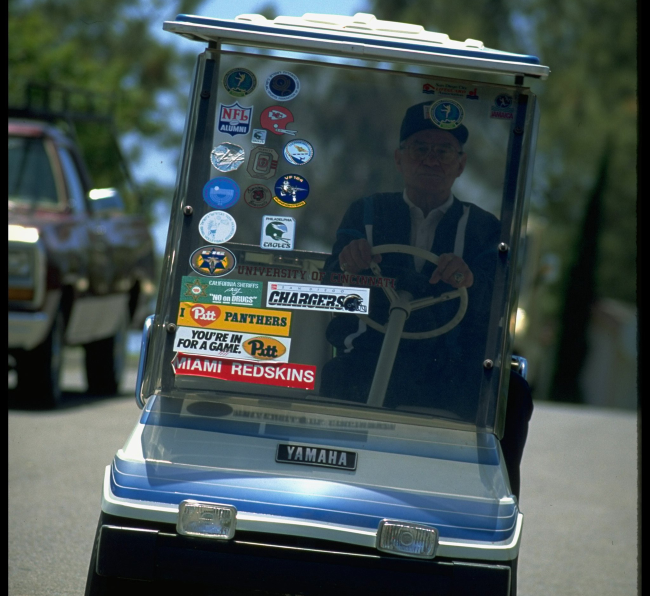 Gillman's golf cart is adorned with stickers of the places he's been.