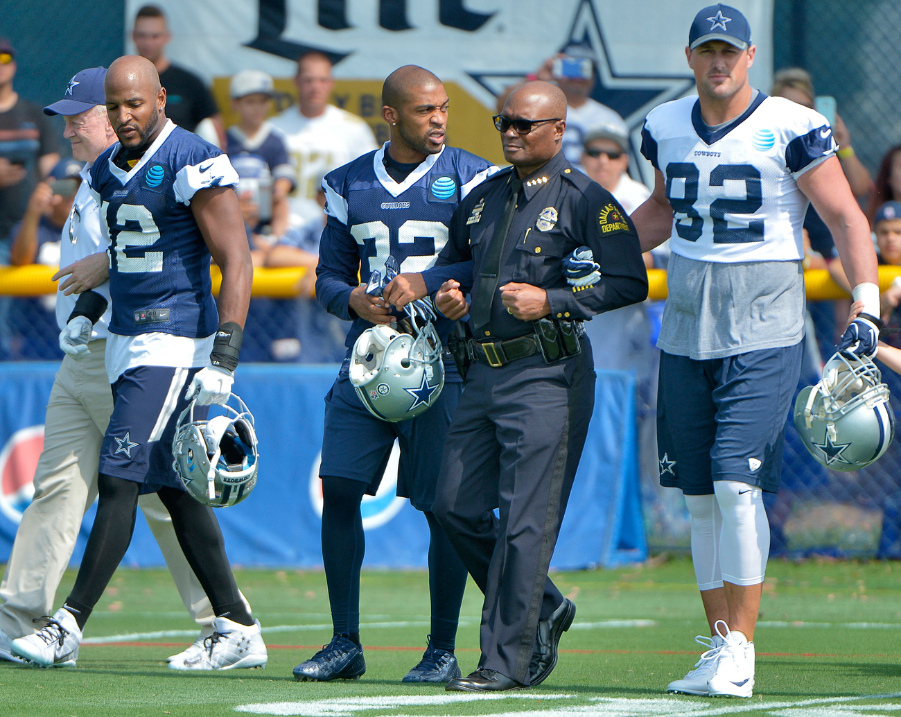 Dallas Police chief David Brown is escorted onto the field by Orlando Scandrick (32) and Jason Witten before Saturday's practice in Oxnard, Calif.