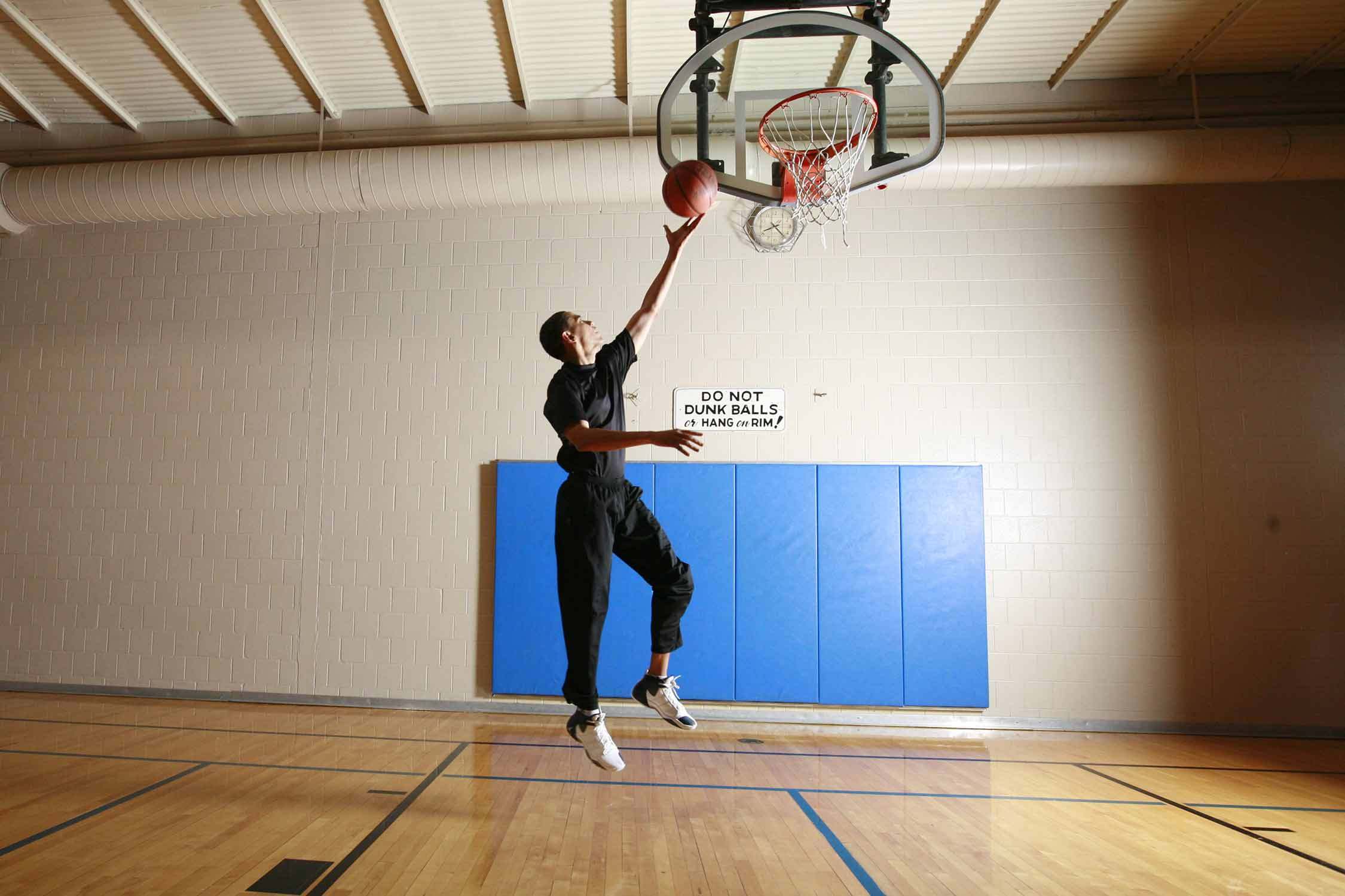 Following the court's rules, Barack Obama lays in a left-handed layup rather than throwing down a slam in 2007.