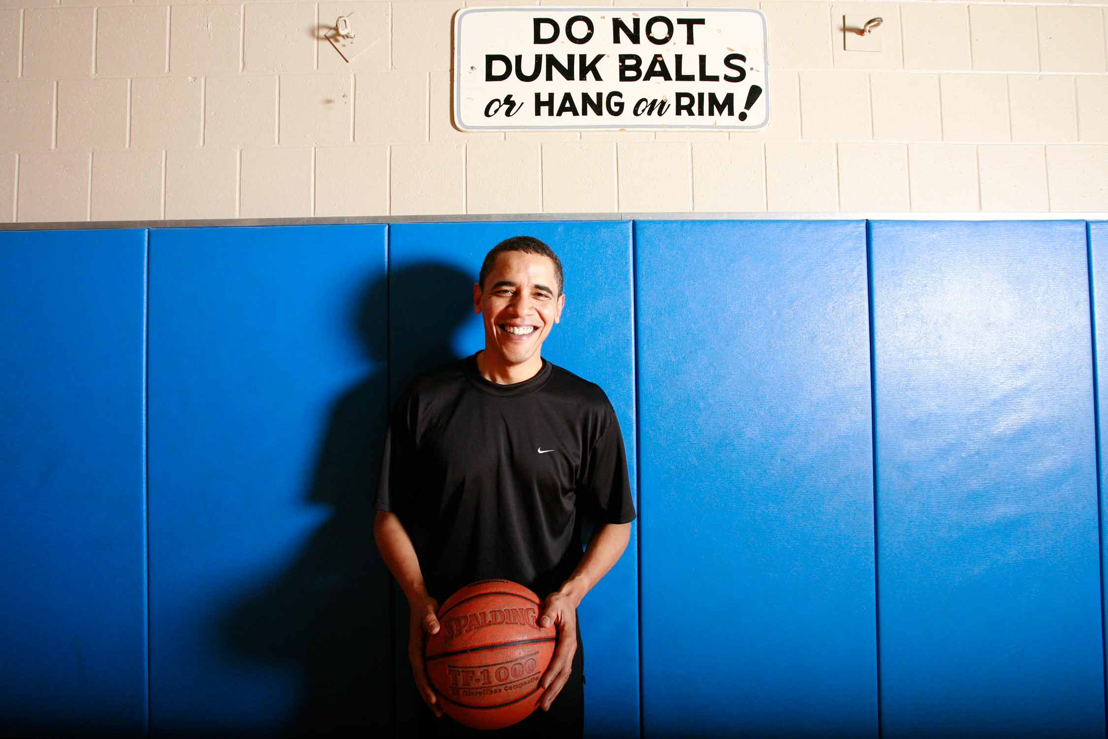 Barack Obama posing in front of a sign at the Illinois YMCA in 2007.
