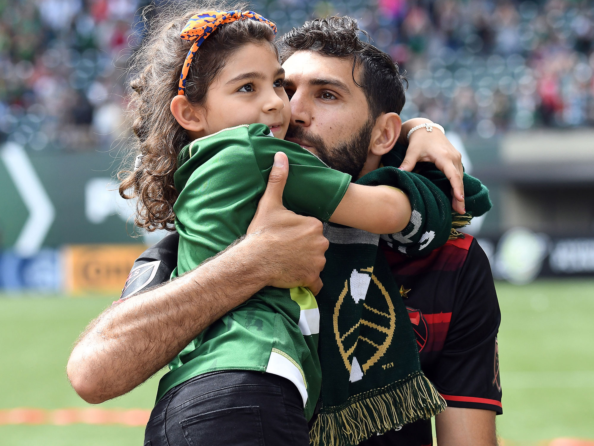 Diego Valeri hugs his daughter after a Portland Timbers victory