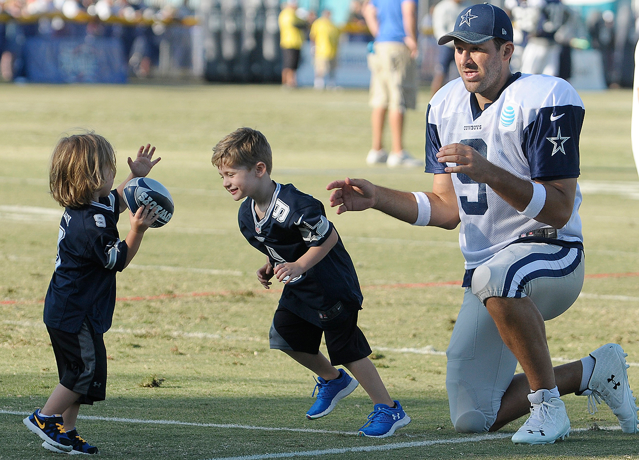 Tony Romo plays catch with his sons Hawkins and Rivers after a recent Cowboys camp practice in Oxnard.