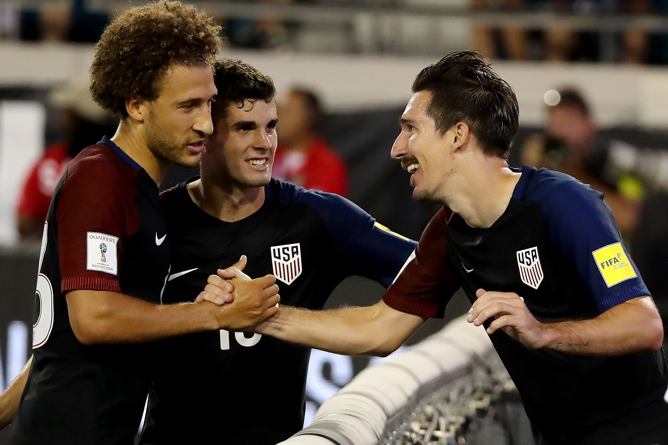 Fabian Johnson, Christian Pulisic and Sacha Kljestan celebrate during a 4-0 win, which cemented the USA's place atop its World Cup qualifying group and a berth in the CONCACAF hexagonal.