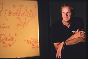 Wyche poses next to a play he drew up for the Bengals in 1989.