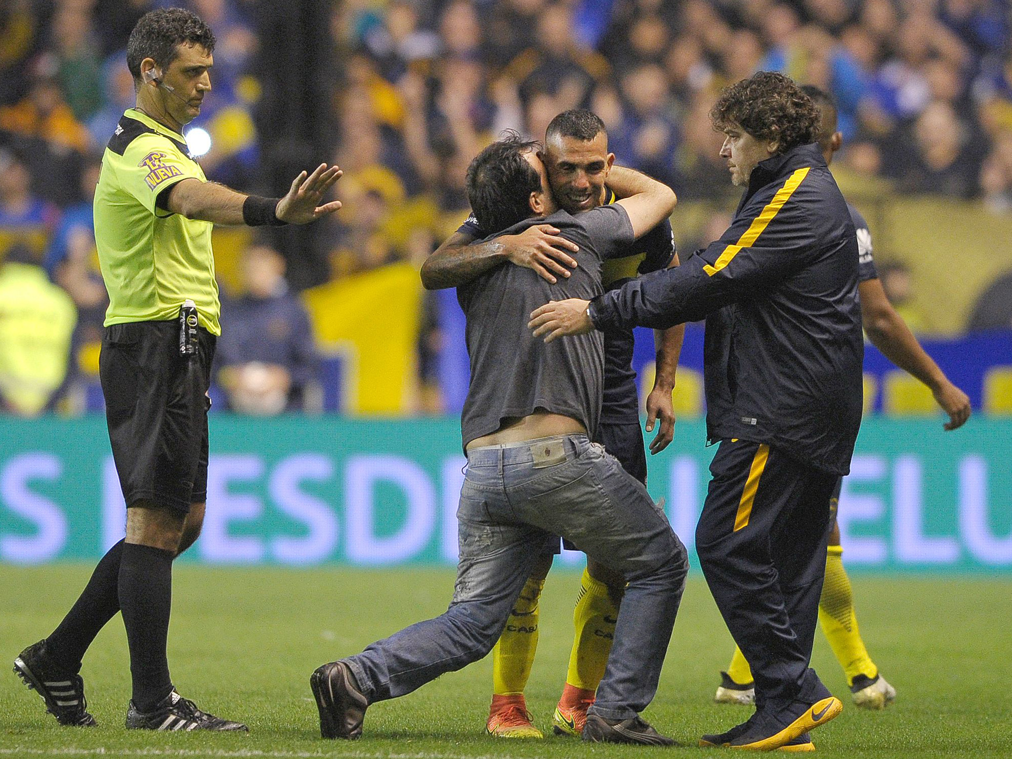 A fan hugs Carlos Tevez on the field at La Bombonera