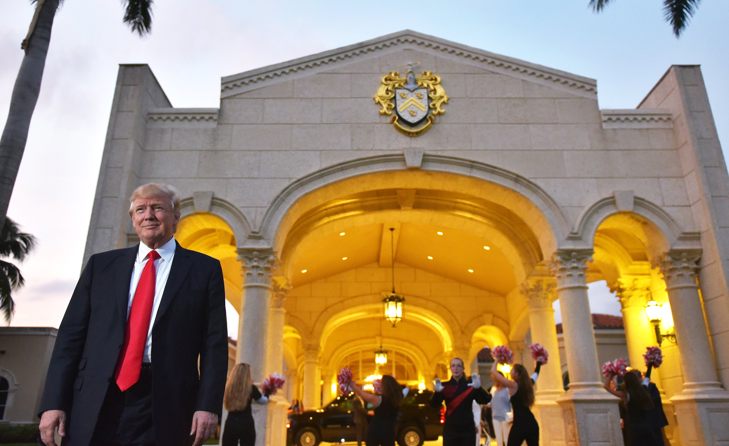 President Donald Trump stands outside Trump International Golf Club on Sunday.